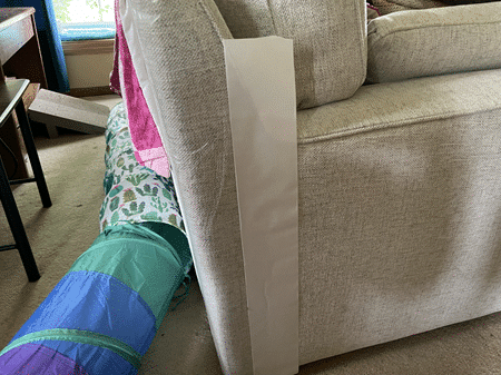 Training Tap on the corner of the couch. The white piece is removed once stuck to the couch, revealing the sticky side.