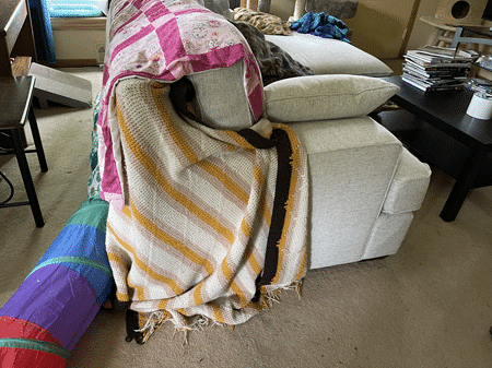 Couch with blankets covering the corner